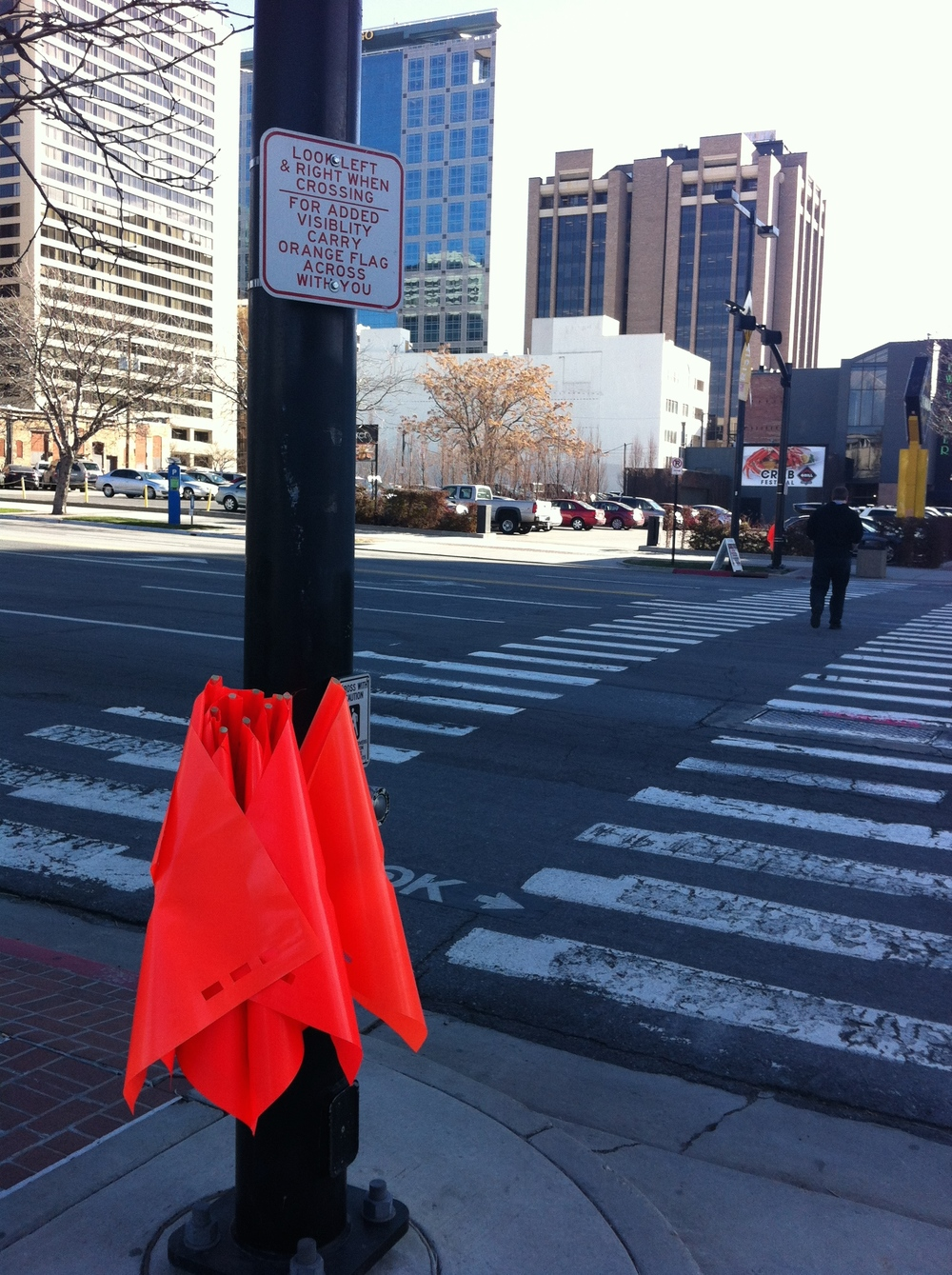 Salt Lake City takes cross walk safety as step further by providing bright orange flags for pedestrians to use as they cross the street. Is this going too far?