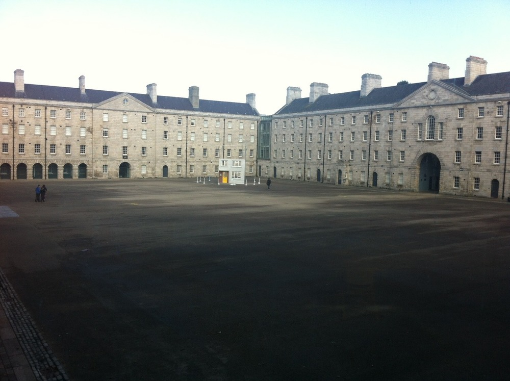 The pebbledash house located at the far corner from the entrance to the museum is dwarfed in the stark parade square.