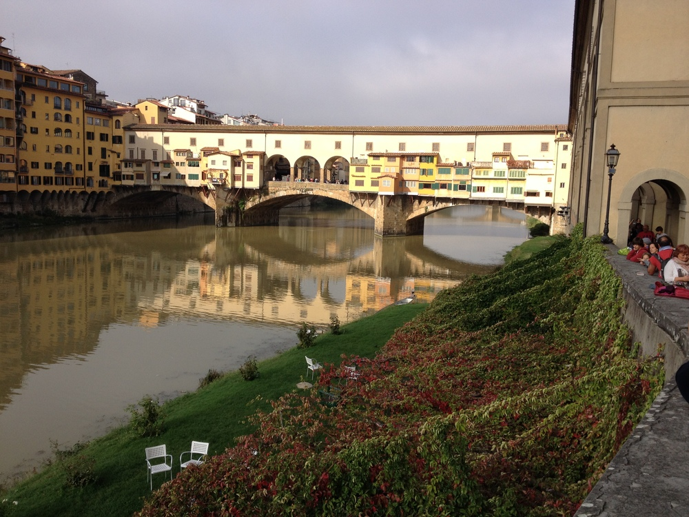 Ponte Vecchio with garden-like river bank and on the right you can see the tourists lined up to enjoy the view of the river, buildings and bridge.