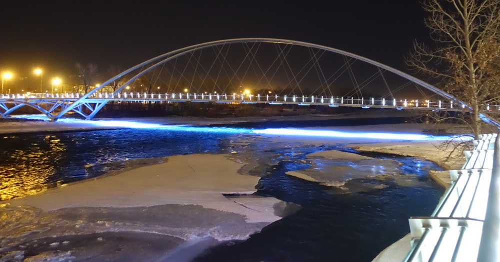The St. Patrick's bridge shines onto the water rather than into the night sky creating an eerie atmosphere.