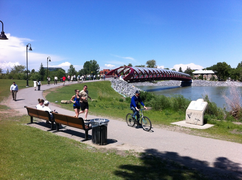 Calgarians love their 800+ kilometres of walking, running and biking pathways.  The red pedestrian bridge in the background is the Peace Bridge designed by the world famous Santiago Calatrava. This is lunch hour downtown!