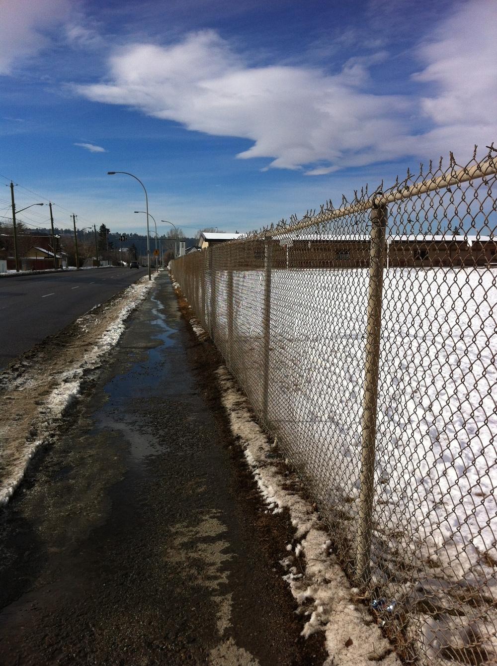 "Kensington Road sidewalk next to school yard fence is a ""mean street."""
