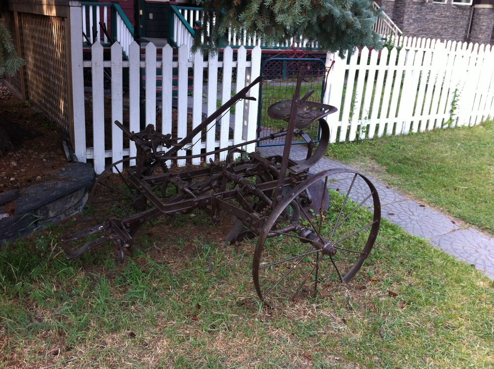 Old agricultural equipment in front yard in Hillhurst.