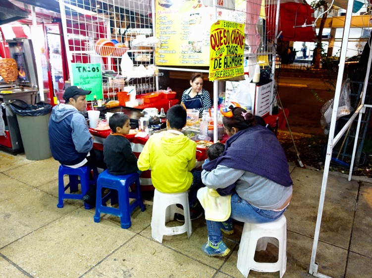 Family dining on the street in Mexico City.