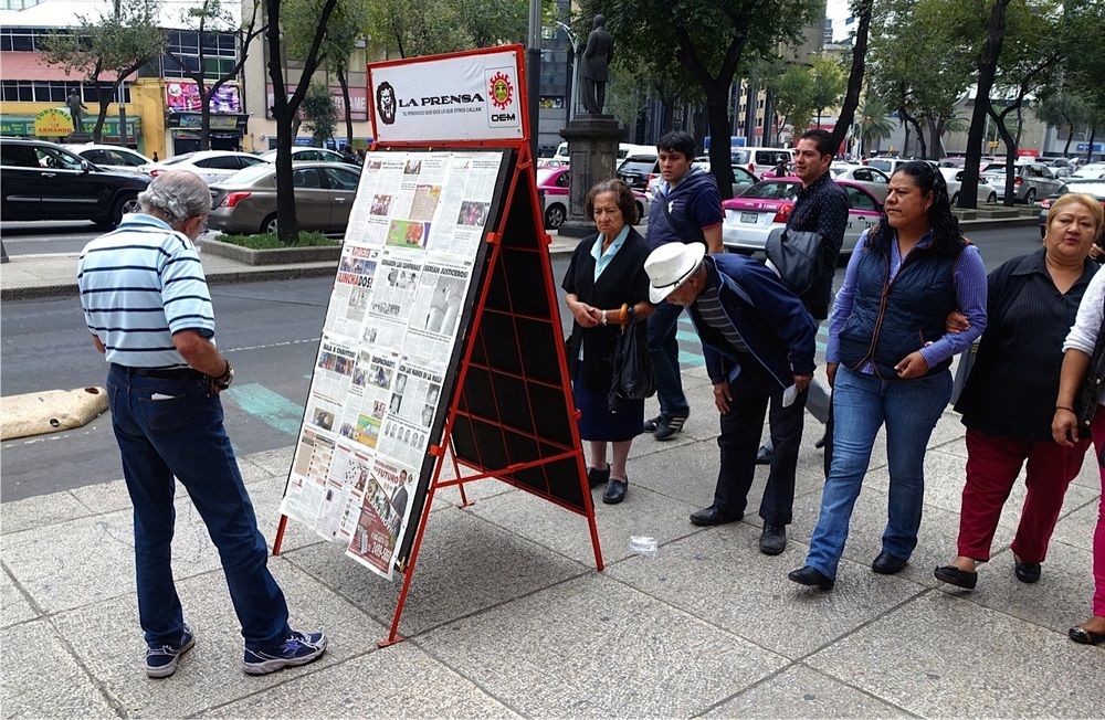 In Mexico City a popular activity is reading the newspaper on the sidewalk.