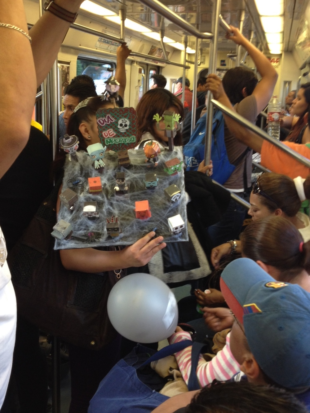 A crowded subway car with vendor selling trinkets for Day of the Dead in Mexico City, mid-afternoon.