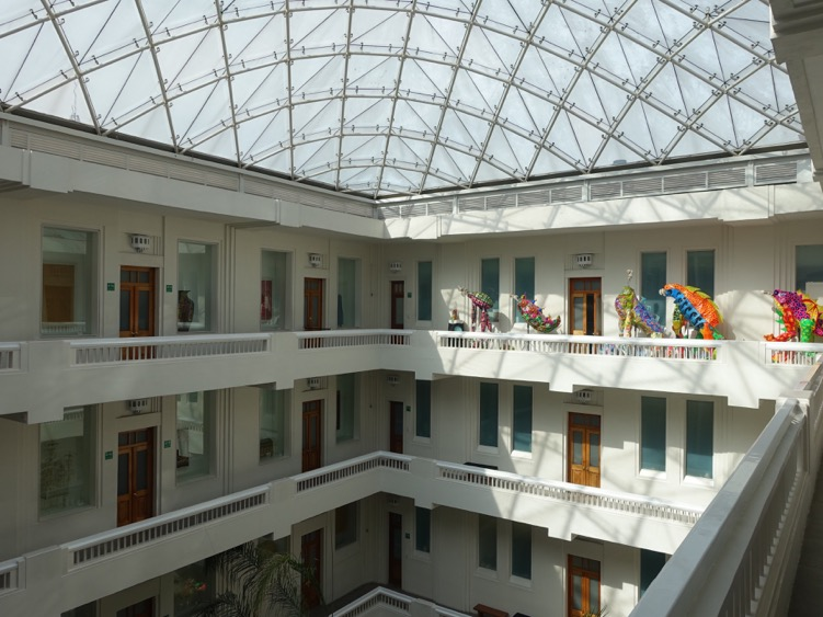 The interior courtyard of the building has been glassed over to create a wonderful gallery space that looks like a modern South Beach Hotel. The colourful Alebrijes creatures in the distance bring the space alive in a fun folk-art manner.