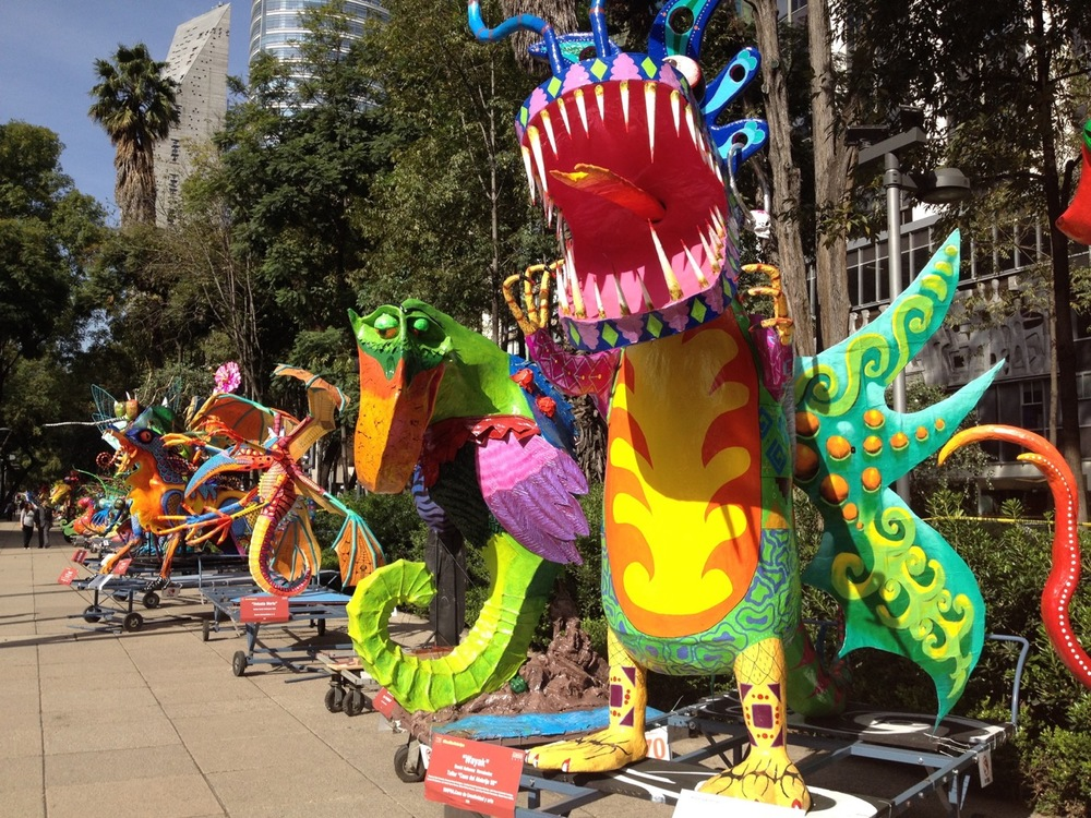The Alebrijes creatures on parade on the sidewalk next to the Angel of Independence monument.