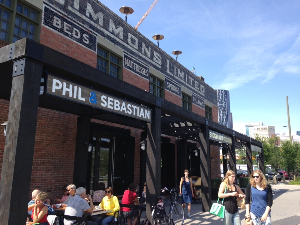 The Simmons Limited warehouse building has been transformed into multi-tenant restaurant, cafe and bakery on RiverWalk next to the Bow River.