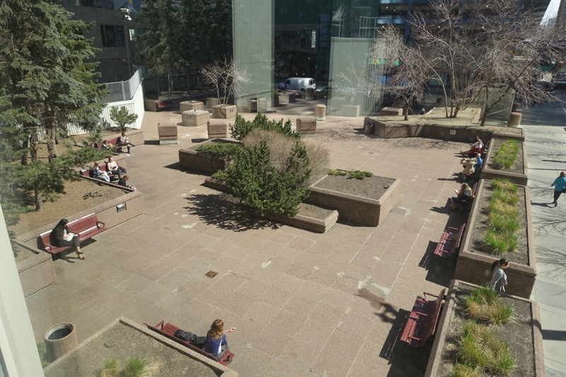A view of the First Canada Centre plaza from the +15 bridge over 7th Avenue.  In the summer, there are lots of planting creating a cheerful and colourful place to sit in the sun at noon hour.