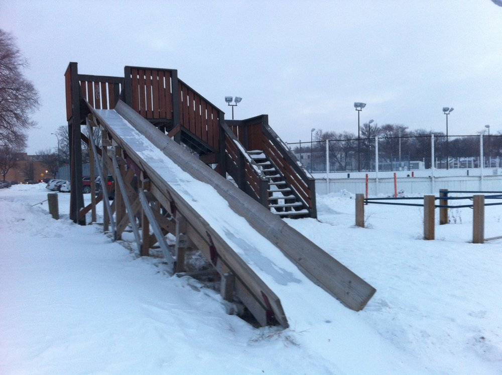 This snow slide in Winnipeg next to an old fashion outdoor hockey rink. I imagine it gets used by siblings who get tired of watching the good old hockey game.  I don't recall seeing one of these in another park.