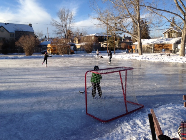 This DIY outdoor rink is being used by two figure skaters, as well as a mom and her son playing hockey and several people watching.  Too bad City of Calgary limits the number of people who get access to fire hydrants for flooding the rink in any one community.  Why can't there be as many ice rinks as there is demand?