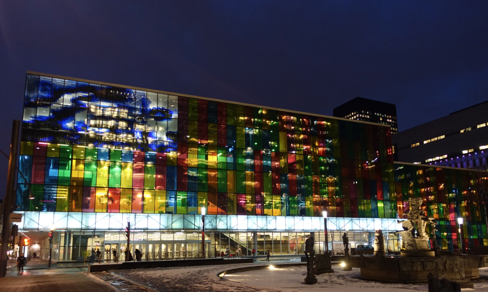 The glass facade of Montreal's Convention Centre at night.