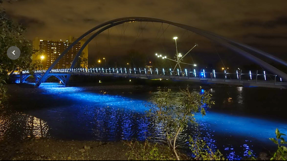 "King Bridge over the Bow River at night, with ""Bloom"" artwork in the background."