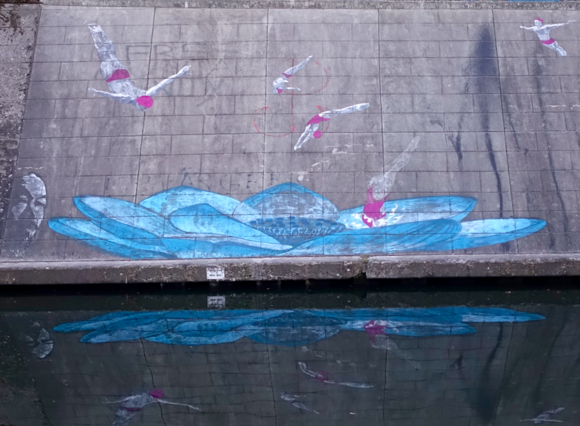 This clever work of art is on the retaining wall of one of the canals. Love the way it uses the reflection in the water to enhance the image.