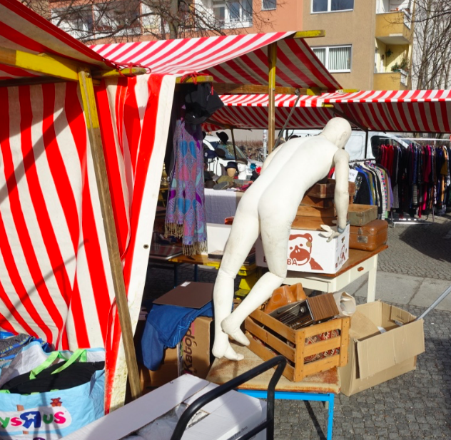 "Liking the flowmarkets where locals rent tables at their nearby ""platz"" aka plaza, park, playground and sell stuff.  It is a bit garage sale, a bit flea market.  Good vibe; this guy is getting right into it."