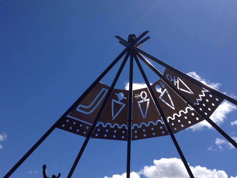 These symbols represent the Five Nations who signed Treaty 7 on 22 September 1877: Siksika (Blackfoot), Kainai (Blood), Piikani (Peigan), Stoney-Nakoda, and Tsuu T'ina (Sarcee).  Link:  Stampede's Iconic Entrance