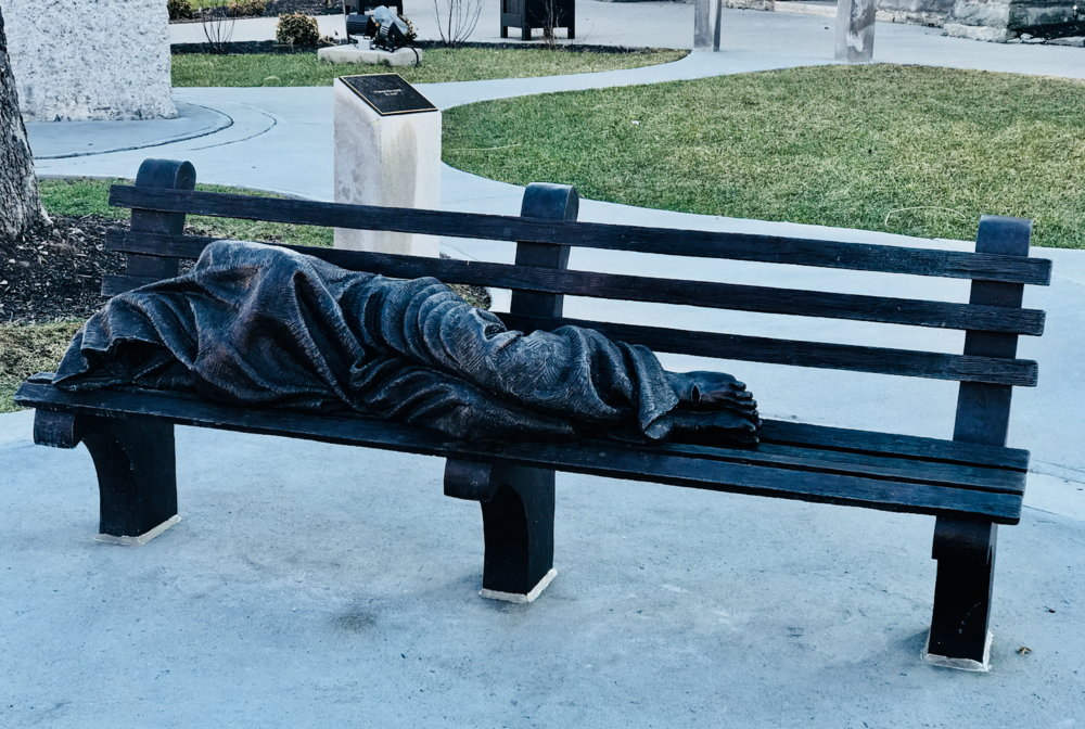 When I first saw this piece I thought it was a real person sleeping on the bench. This is outside St. Patrick's Roman Catholic Church.