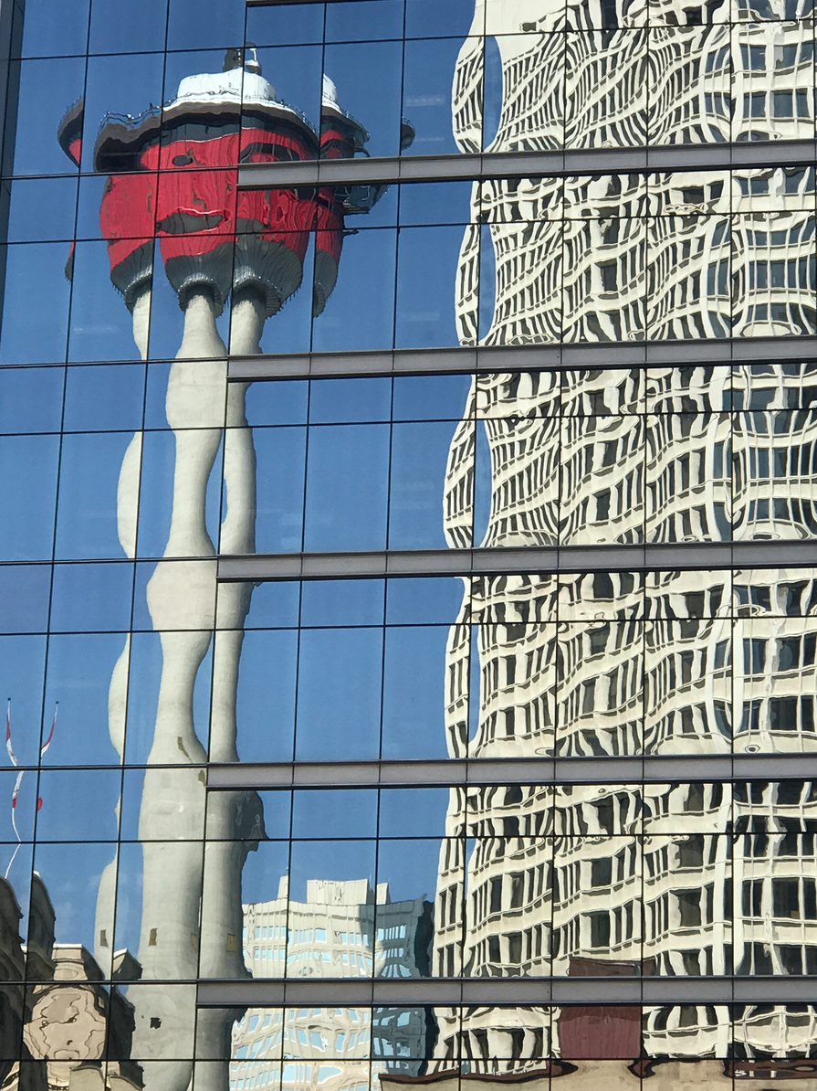 Calgary Tower and Scotia Centre take on a Salvador Dali-like metamorphosis when reflected in the glass facade of another building.