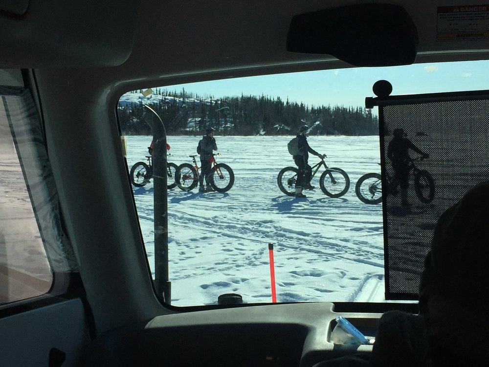 Winter bikers passing the sno-bear.