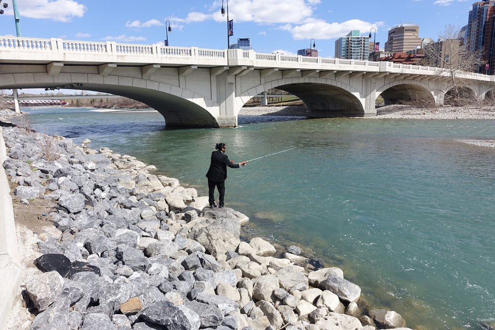 How cool is this fisherman, dressed up in a suit fishing on the shore of the Bow River at the Louise Bridge, that connects Kensington to downtown