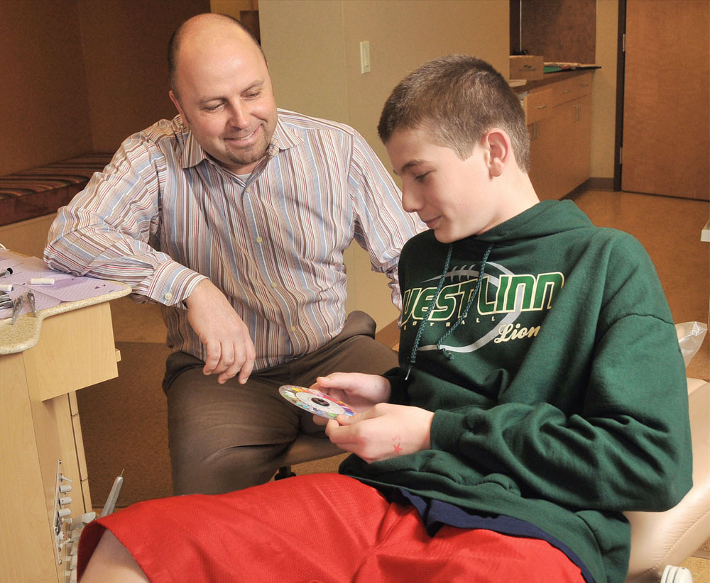 Dr. Chris Sierk patiently waits as Kaleb Brusa, 13, chooses a color for the elastics on his braces.