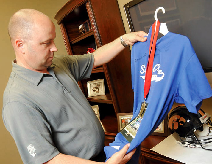 Dr. Chris Sierk holds up a jersey from one of the baseball teams he recently sponsored.