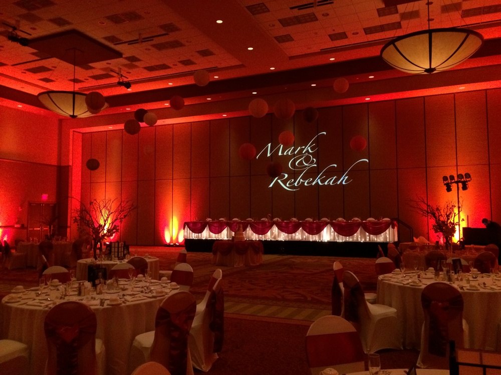Mark & Rebekah worked with  Create-A-Scene  to design a beautiful reception at  Embassy Suites  in East Peoria, IL  with DJ4U providing the name in lights projection and cranberry/orange perimeter lighting.