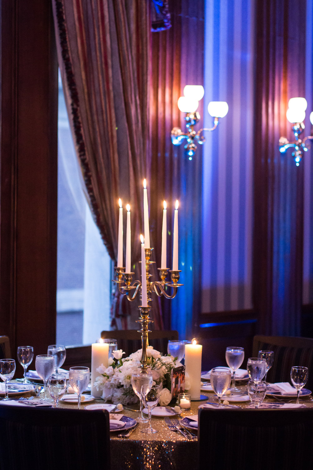 Ornate candelabrum and white floral arrangements to illuminate the room