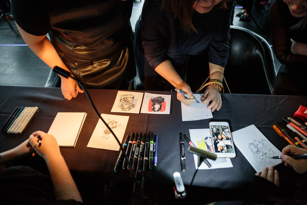 Professional caricature artists creating anime portraits