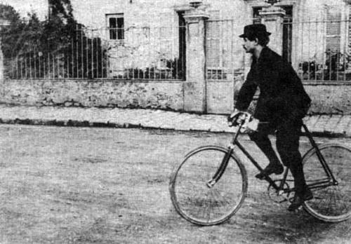 Alfred Jarry rides bike (with gun in back pocket).