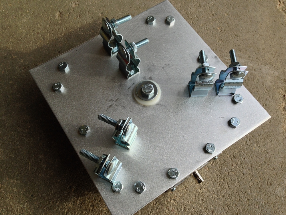 """Bottom of the base showing the conduit hangers and the insulated 3/8"""" mount"""