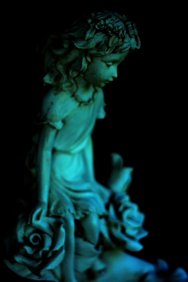 A photograph of a statue of a girl wih roses