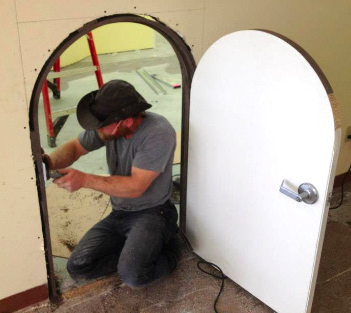 Carpenter installing custom build children's' door.