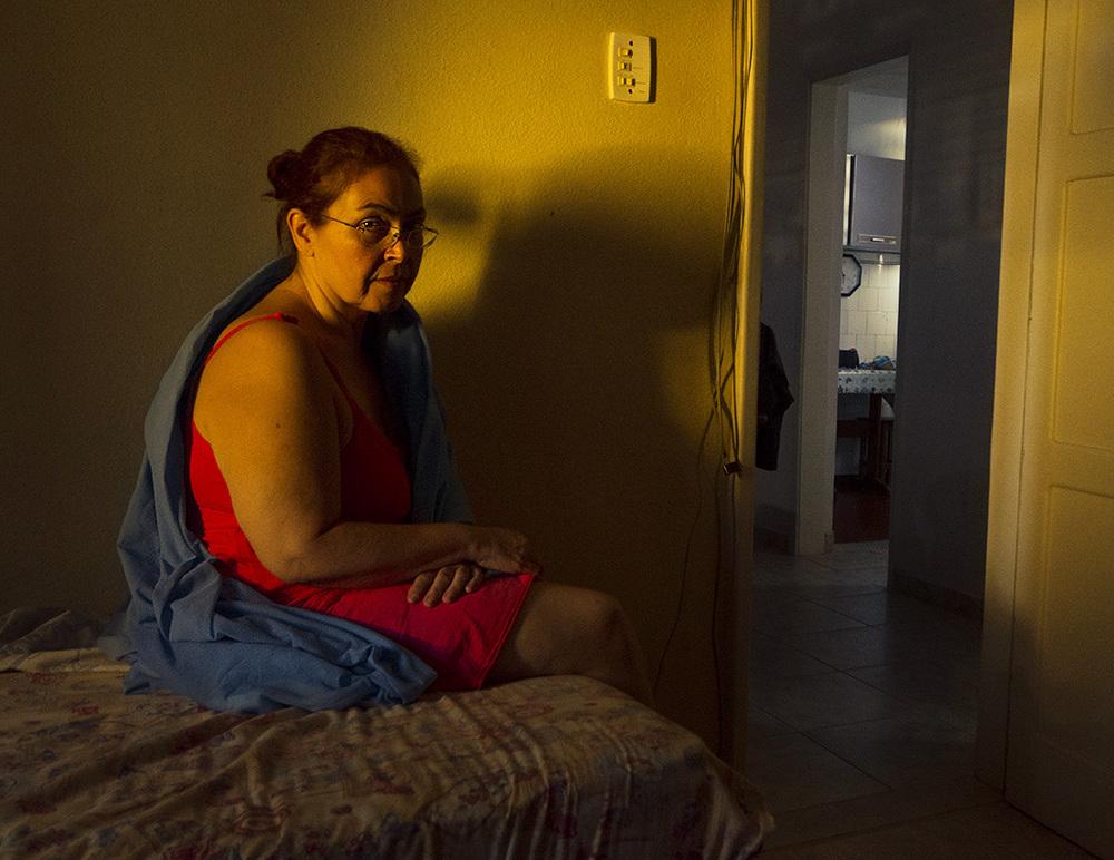 Mãe iluminada pela luz do sol rebatida na casa amarela do vizinho.