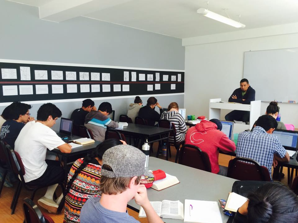 Students pause for a moment of prayer before a Lectures in Ministry class presented by Manolo Matos, pastor of Calvary Chapel Lima