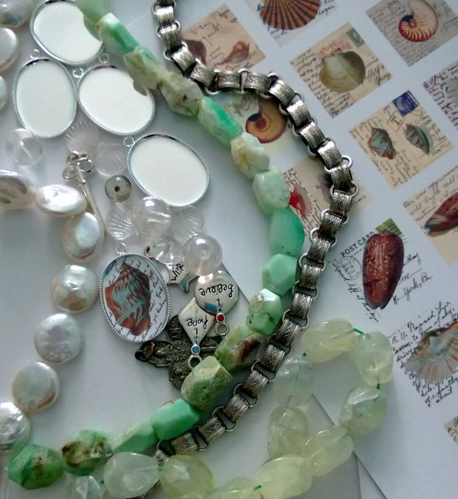 Gathering materials for the bracelet.  Pearl disks, green stones, glass and metal charms, shell images for the pendants and silver book chain for the base.
