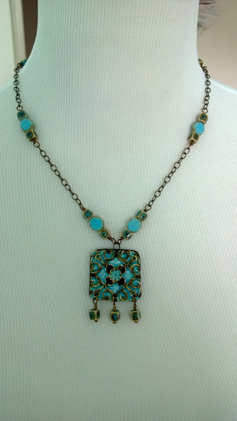 Turquoise and chocolate focal paired with porcelain cubes and picasso discs on bronze finish chain.