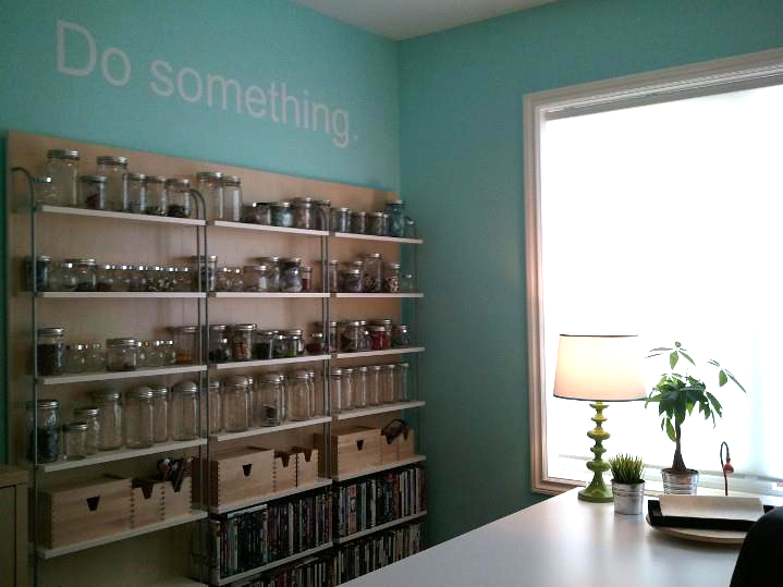 Wall storage repurposed from old CD/DVD shelves.  Mason jars, recycled glass jars for bead and finding storage and lots of natural light.   Vinyl signage with important message.  xD