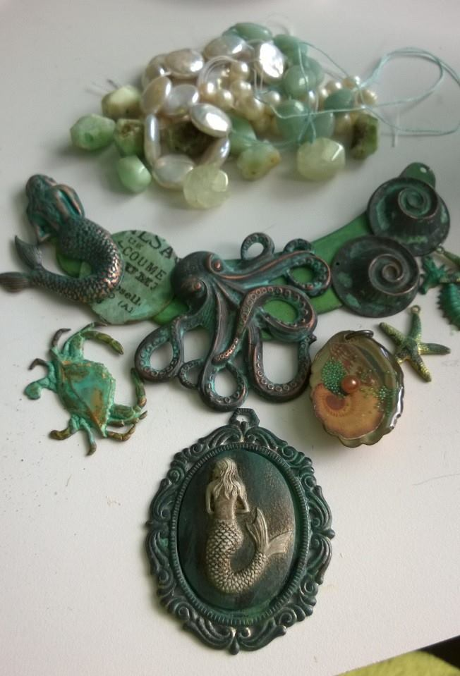 "Once the pieces were dry, I started playing with placement. I had originally intended to use the mermaid cameo, but she was too ""muddy"" and blended too much with all the other elements in the collage. I needed something with more pop. I was also pulling pearl and stone beads that would make a nice compliment to the metal pieces."