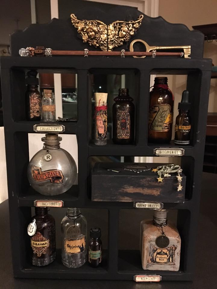 I added some embellishments on the bottles, found some other fun stuff to use with the cabinet including a brass key, one of the wands I'm working on and an old moon and stars pin that has a great patina. Time to put it all together... looking pretty good, but it needs a back, I'm thinking!