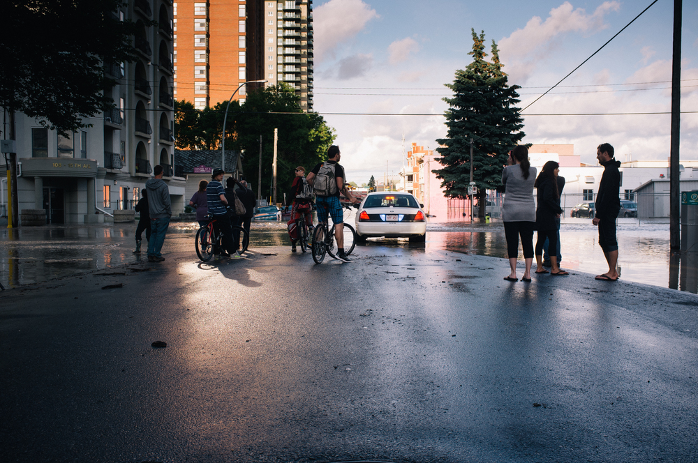 Sightseers. Centre Street at 15 Ave SW, facing the Stampede Grounds. Around the corner, a car was swamped; much debris had accumulated around it in the heavy, northbound current.