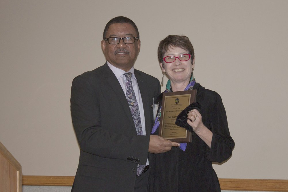 FRHA President Michael Ham-Ying presents Gail Bellamy the 2017 Wendell Rollason Award. Bellamy, of the Florida Blue Center for Rural Health Research and Polcy, is also a longtime FRHA board member.