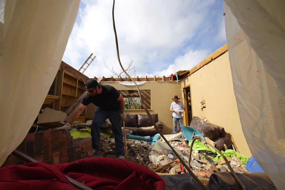 A volunteer clears bricks from the living room of a homeowner in Moore. The storm sheered off the top floor of the home.