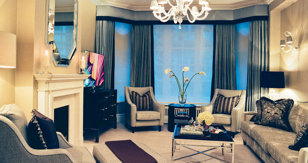 Silk curtains, textured wallpaper and Murano glass chandelier and wall lights all help to create this elegant and sophisticated living room.