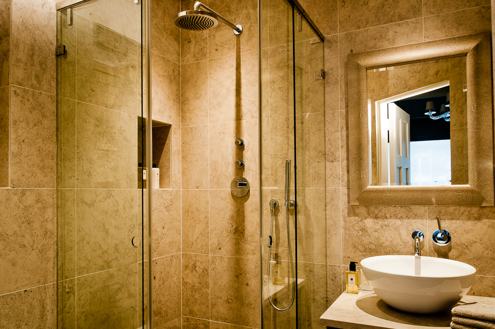 Limestone en-suite bathroom with bespoke made shower screen.