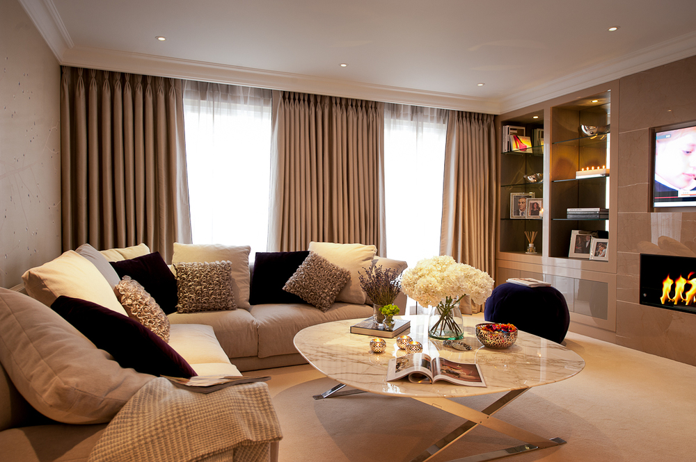 Luxuriously comfortable living room with bespoke joinery and marble fireplace.