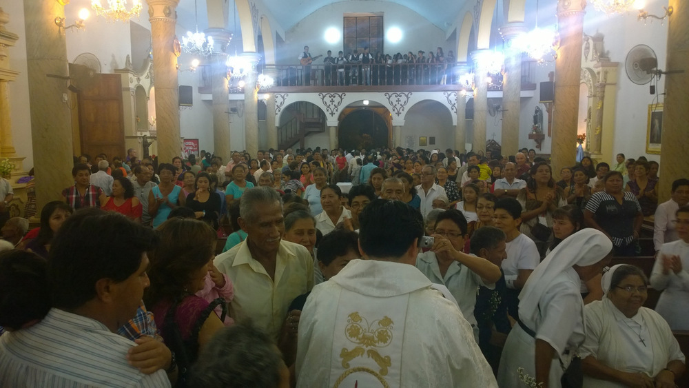 A Young Peruvian Augustinian Priest greets his family following his first mass after ordination in 2013