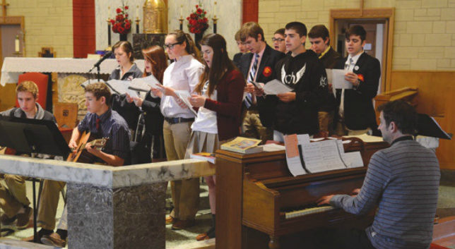 Fr. Brian (at the piano) encourages student participation in music ministry for the school Masses and prayer services.