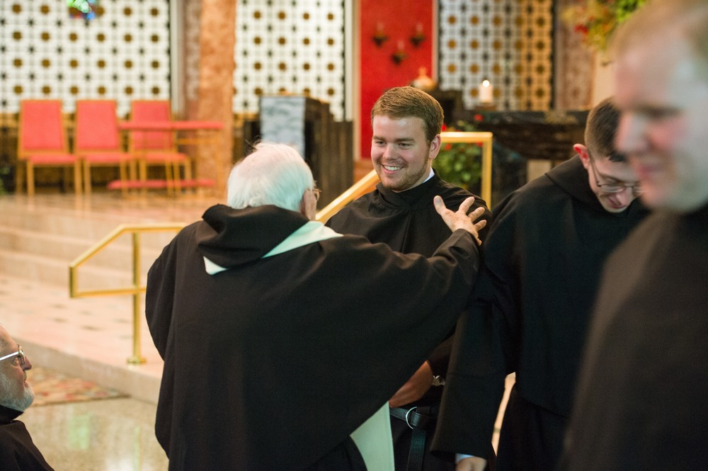 Brother Jeff Raths, O.S.A., embraces Fr. John Flynn, O.S.A., in his newly vested black habit